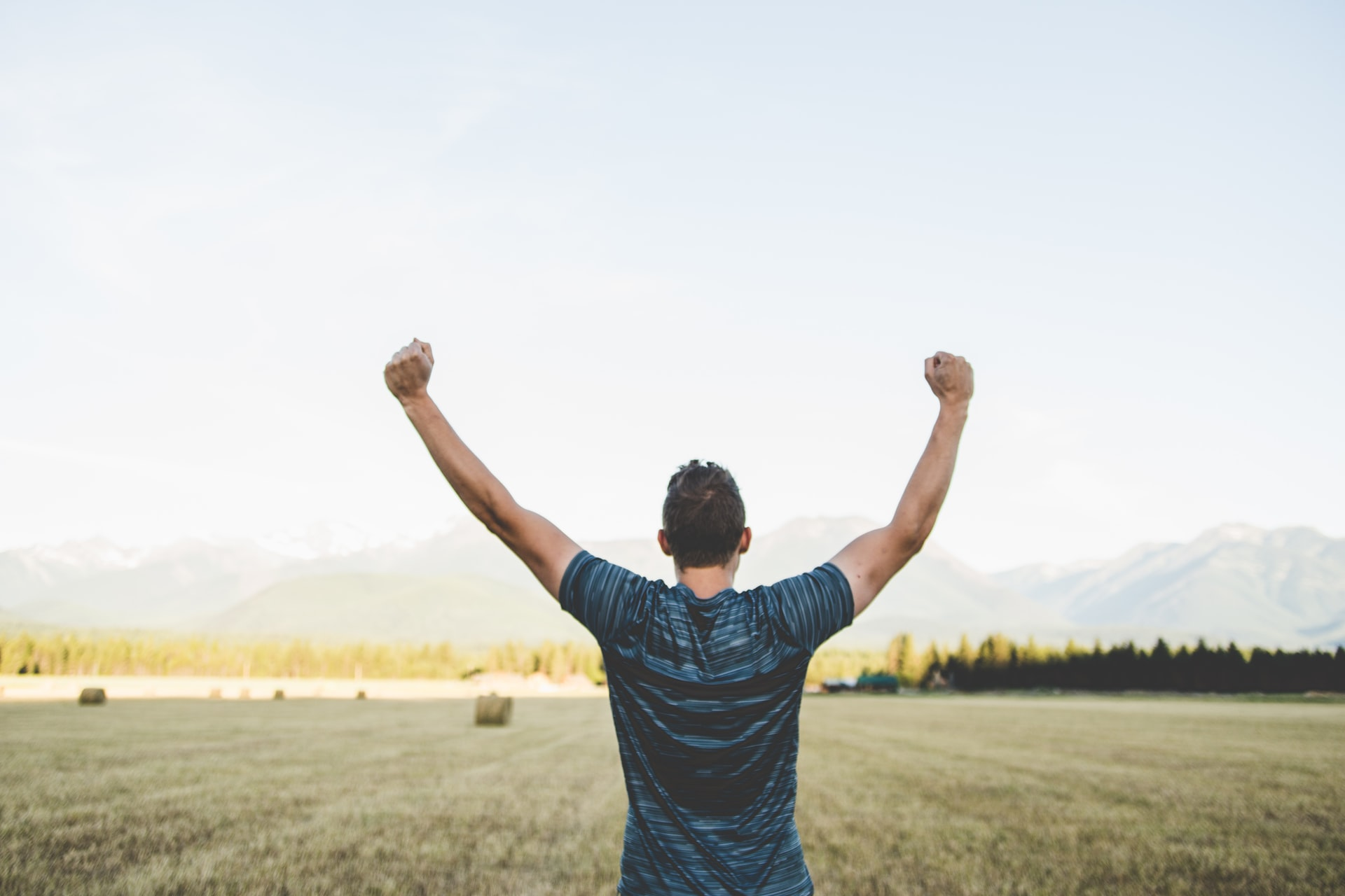 Joyful man with hands raised up